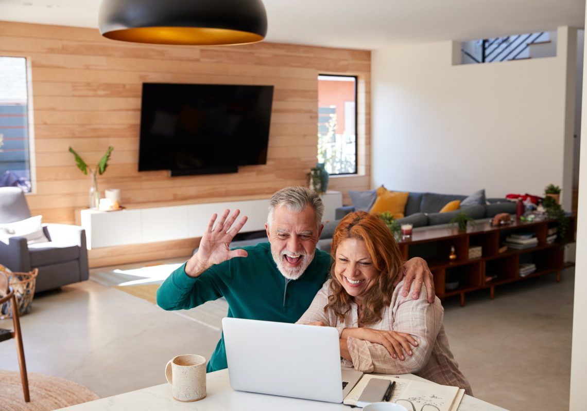 senior-hispanic-couple-at-home-with-laptop-having-video-chat-with-family.jpg